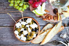 Glass with white wine, grape, cheese, over rustic wooden backgro Royalty Free Stock Image