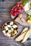 Glass with white wine, grape, cheese, over rustic wooden backgro Stock Image