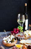 Glass with white wine, grape, cheese, over rustic wooden backgro Royalty Free Stock Photos