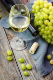 A glass of white wine and grape on old wooden table Royalty Free Stock Images