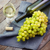A glass of white wine and grape on old wooden table Stock Photos