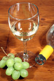 Glass of White Wine and Grapes. This is an image of a glass of white wine with green grapes and the top of a wine bottle royalty free stock image
