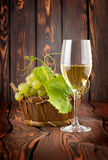 Glass of white wine and grapes Stock Image