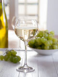 A glass of white wine. With grapes in the background Royalty Free Stock Images