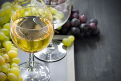 Glass of white wine and grapes on a blackboard, horizontal Stock Images