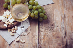 Glass of white wine, grapes, cashew nuts and soft cheese. A glass of white wine, grapes, cashew nuts and soft cheese on a wooden board, rustic style background Stock Images