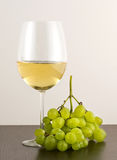 Glass of white wine with green grapes Royalty Free Stock Images