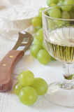 Glass of white wine, green grapes and soft French cheese Coulomm Royalty Free Stock Image