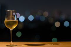 A glass of white wine and its shadow on wooden table of rooftop bar with colorful bokeh of city light and space for text royalty free stock photos