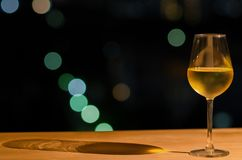 A glass of white wine and its shadow on wooden table of rooftop bar with colorful bokeh of city light and space for text royalty free stock photo