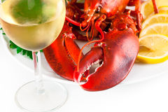 Glass of white wine with lobster. Glass of white wine with cooked lobster on the plate, top view Stock Image