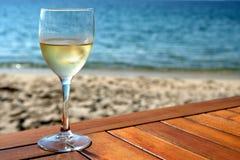 Glass of white wine on mediterranean beach table. Glass of white wine on mediterranean beach stock photos