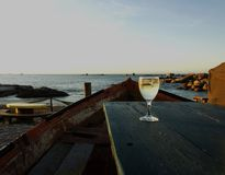 Glass of white wine on the old boat at sunset, selective focus. Glass of white wine on the old boat table in a cafe on the beach at sunset, selective focus royalty free stock photos