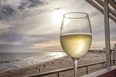 Glass of white wine overlooking the beach with sunset Stock Images