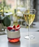 A glass of white wine and a panakota dessert stock image