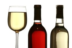 Glass of white wine, with red and white wine bottles. Glass of white wine standing on table with red and white wine bottles forming a pattern, isolated on white Stock Photo