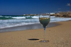 Glass of white wine on the seashore against a blue sky. Stock Photo