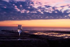 A glass of white wine at the seaside sunrise background. Romantic glass of wine sitting on the beach at colorful sunset Glasses of white wine against sunset stock photos