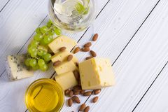 Glass of white wine with snacks - various types of cheese, figs, nuts, honey, grapes on a wooden boards background. Top view royalty free stock image