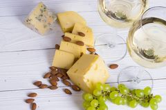 Glass of white wine with snacks - various types of cheese, figs, nuts, honey, grapes on a wooden boards background. Top view stock photo