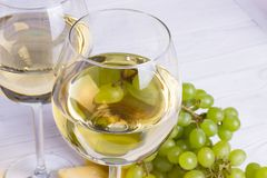 Glass of white wine with snacks - various types of cheese, figs, nuts, honey, grapes on a wooden boards background. Top view stock image