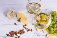 Glass of white wine with snacks - various types of cheese, figs, nuts, honey, grapes on a wooden boards background. Top view stock photography