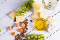 Glass of white wine with snacks - various types of cheese, figs, nuts, honey, grapes on a wooden boards background. Top view royalty free stock photos