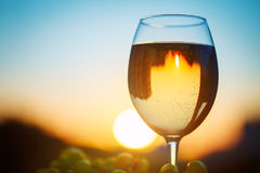 A glass of white wine at sunset, with the reflection of the houses. Stock Photo