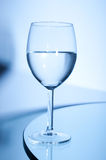 Glass of white wine on the table. On blue background Stock Photo