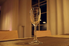 Glass for white wine on the table in restaurant at night Stock Photos