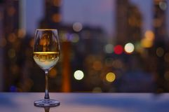 A glass of white wine on table of rooftop bar royalty free stock photography