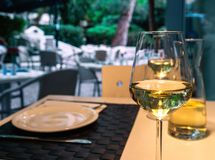A glass of white wine on a table in a street cafe royalty free stock photos