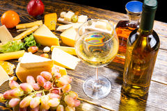 Glass of White Wine on Table with Various Cheeses Stock Images