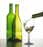 Glass of white wine with two green wine bottles Royalty Free Stock Photography