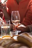 A glass of white wine in a woman's hand. Wine tasting. stock photo