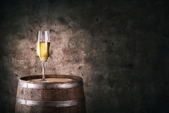 Glass of white wine on wooden barrel Royalty Free Stock Images