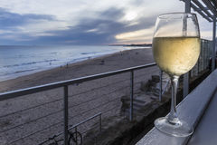 Glass of white wine on a wooden bench overlooking the beach with Royalty Free Stock Photos