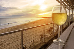 Glass of white wine on a wooden bench overlooking the beach with. Sunset stock photo