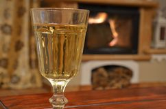Glass of white wine on wooden table. Ahead fireplace Stock Images