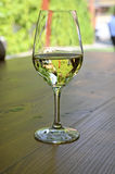 Glass of white wine on wooden table Royalty Free Stock Photos