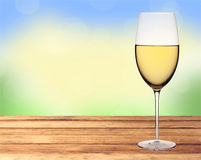 Glass of white wine on wooden table over nature background Royalty Free Stock Photos