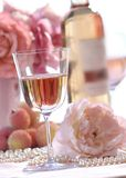 Glass of white zinfandel-1. Glass of white zinfandel and bottle on talbe with flowers and pearls Royalty Free Stock Photos