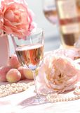 Glass of white zinfandel-3. Glass of white zinfandel with bottle and flowers as background,table top Royalty Free Stock Image