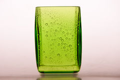 Glass whith drops. A green glass whith drops Stock Image