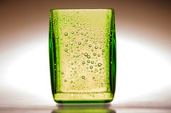 Glass whith drops. A green glass whith drops Stock Photos