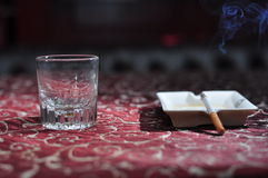 A glass wind and burning cigarette Stock Photos