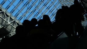 The glass window airport ecsalator with moving silhouette of people. Traveling concept: elevated male and female travellers group flying with transit airline stock video