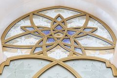 Glass window decorated with golden geometric form in Sheikh Zayed Grand Mosque with blue sky in the morning at Abu Dhabi, UAE Royalty Free Stock Image