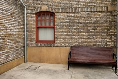 Glass window on Old brick wall and big wooden chair. Perspective view with retro style building Stock Photography