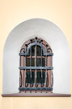 Glass window sill behind bars in the form of an arch in a historical building in Lviv, Ukraine. Glass window sill behind bars in the form of an arch in a Stock Photo